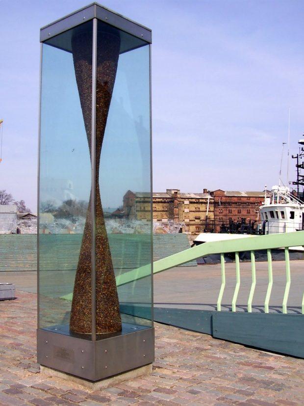 Vides objekts Dzintara pulkstenis, 2004. Rūdīts stikls, tērauds, dzintars, 400x95x95cm. Vecās ostmalas promenāde, Liepāja, Latvija.